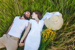 Happy young relaxed couple in love laying down on the grass overhead Stock Photo