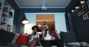Happy young relaxed multiethnic man and woman sit together at home watching TV series, eating popcorn slow motion. stock video footage