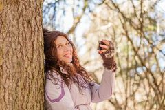Happy young retired woman. In the mountains a young retired woman is taking selfie and happy while she breathes deeply and enjoying the holidays royalty free stock image