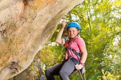Happy young rock climber in helmet abseiling stock images