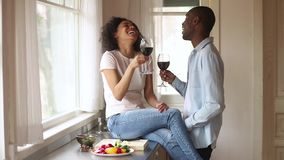 Happy african couple clinking glasses talk laugh bonding in kitchen. Happy young romantic african couple in love clinking glasses having fun talk laugh bonding stock footage