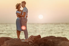 Happy young romantic couple relaxing on the beach and watching the sunset Royalty Free Stock Images