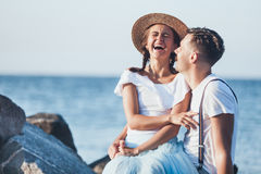 Happy young romantic couple relaxing on the beach and watching the sunset. Happy young romantic couple relaxing on the beach watching the sunset Royalty Free Stock Photos