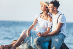 Happy young romantic couple relaxing on the beach and watching the sunset Royalty Free Stock Photo