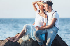Happy young romantic couple relaxing on the beach and watching the sunset. Happy young romantic couple relaxing on the beach watching the sunset Stock Photo