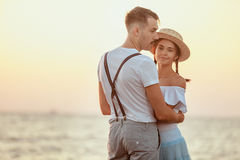 Happy young romantic couple relaxing on the beach and watching the sunset Stock Photos