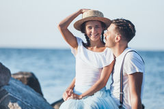 Happy young romantic couple relaxing on the beach and watching the sunset Stock Photography