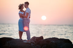 Happy young romantic couple relaxing on the beach and watching the sunset Stock Image