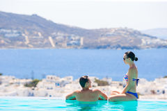 Happy young romantic couple relaxing on the edge of swimming pool. Lovely young romantic couple relaxing by swimming pool Stock Photos