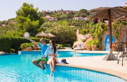 Happy young romantic couple relaxing near swimming Royalty Free Stock Images