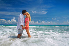 Happy young romantic couple standing on the beach and kissing ea. Young romantic couple enjoy a tender moment of kissing and standing on the beach. Romantic Royalty Free Stock Images