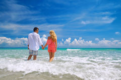 Happy young romantic couple standing on the beach and looking at. Young couple holding hands at beach enjoying romance. Young happy couple in love on romantic Royalty Free Stock Photography