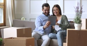 Happy 30s couple using tablet computer on moving day