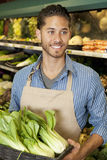 Happy young sales clerk holding bok choy in supermarket Royalty Free Stock Image
