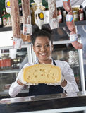 Happy Young Saleswoman Holding Cheese At Counter Royalty Free Stock Photo