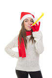 Happy young Santa girl with party blower Royalty Free Stock Photography