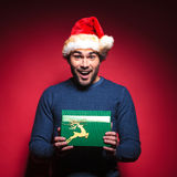Happy young santa man holding a green gift. Stock Photo