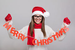 Happy young Santa woman holding Merry Christmas text decoration Stock Images