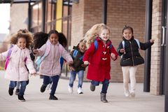 Happy young school girls wearing coats and carrying schoolbags running in a walkway with their classmates outside their infant sch. Ool building stock image