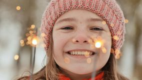 A happy young schoolgirl with sparkling sparks of bengal lights among the winter forest. Face close-up. On the eve of stock image