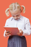 Happy young schoolgirl using tablet PC over orange background Stock Photos