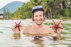 Happy young scuba diver holding sea star, smiling, looking at camera royalty free stock photo