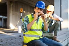 Happy young and senior engineer worker sitting at building site on break royalty free stock photography