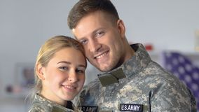 Happy young serviceman and woman looking camera, military couple, american army stock footage