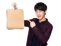 Happy young shopper with finger point to paper bag Stock Image