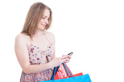 Happy young shopper with gift bags texting on cellphone Royalty Free Stock Photography