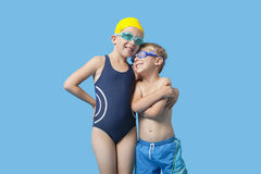 Happy young siblings in swimwear with arm around over blue background Stock Photos