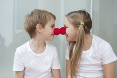 Happy young siblings in white tshirts rubbing clown noses against each other royalty free stock photo