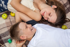 Happy young sister and brother posing lying down on plaid. royalty free stock photos