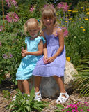 Happy young sisters in park. Two happy young girls wearing pretty dresses with colorful flowers in background Stock Image