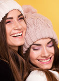 Happy young sisters twins posing. Happy young twins sisters posing, wearing fashionable caps. Yellow background royalty free stock image