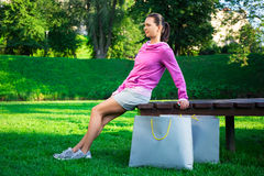 Happy young slim woman in sportswear sitting in park with shoppi Stock Photo