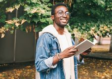 Happy young smiling african man holds book in autumn royalty free stock image