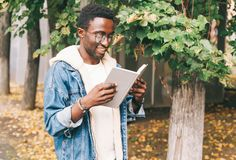 Happy young smiling african man reading book in autumn park stock photo