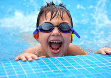 Happy young smiling boy in the swimming pool. Happy young smiling boy in blue swimming pool Royalty Free Stock Image