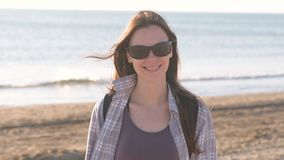 Happy young smiling brunette woman in sunglasses at sand beach by the sea. stock footage