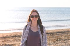 Happy young smiling brunette woman in sunglasses at sand beach by the sea. royalty free stock photo