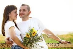 Happy young smiling couple with flowers Stock Photo
