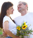 Happy young smiling couple with flowers Stock Image