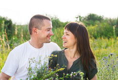 Happy young smiling couple with flowers Royalty Free Stock Photography