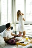 Happy young smiling couple having romantic breakfast in bed Royalty Free Stock Photography