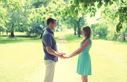 Happy young smiling couple in love, holds hands, relationships, date, wedding - concept, vintage soft colors. Sunny silhouette at park Stock Photos
