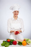 Happy young smiling female cook holding fresh cayennes Stock Photo