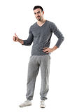 Happy young smiling fitness male model showing thumb up gesture looking at camera. Full body length portrait isolated on white studio background Royalty Free Stock Image