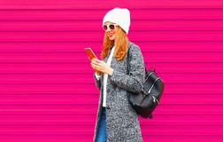 Happy young smiling girl student with phone wearing coat jacket, hat, backpack walking on city street,. Colorful pink wall background stock images