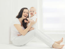 Happy young smiling mother with baby at home in white room Royalty Free Stock Photos